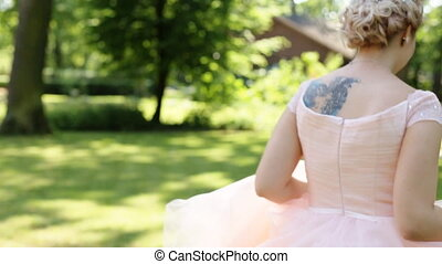 Gorgeous stylish blonde bride in vintage white dress and with tattoo on shoulder running in the park, view from behind