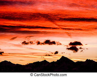 gorgeous sunset sky over jagged mountain landscape silhouette