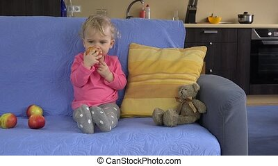 Gorgeous toddler kid child sitting on the sofa and eating big apple fruit.