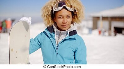 Gorgeous trendy young woman with her snowboard