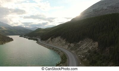 Gorgeous View of Glacial Lake and Scenic Road at Sunset. Aerial Drone Shot. Northern Rocky Mountains, British Columbia, Canada.