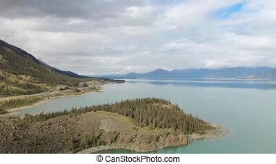 Gorgeous View of Scenic Island surrounded by Turquoise Lake and Mountains in Canadian Nature. Aerial Drone Shot. Yukon, Canada.