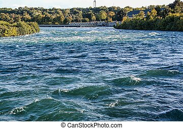 Gorgeous view of the natural landscape. Wide river with green trees on the coastline. Niagara falls. Ontario. Canada. Beautiful nature backgrounds.