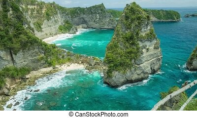 Gorgeous view to rolling waves, to the cliffs and sandy beach on the bottom with clear transparent ocean water in Nusa Penida, North Coast, Bali, Indonesia