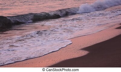 Gorgeous waves form foam on the sandy beach in the rays...