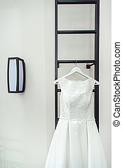 gorgeous white wedding dress on a fire ladder at the balcony. brides accessories in a wedding day