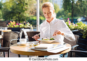 Gorgeous woman eating salad in cafe during lunchtime -...