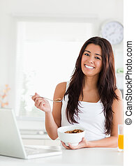Gorgeous woman enjoying a bowl of cereal while relaxing with her laptop in the kitchen