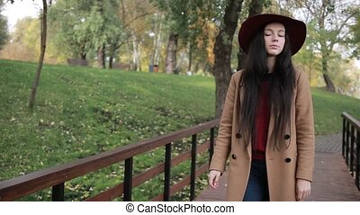 Gorgeous woman enjoying leisure in autumn park