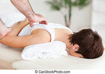 Gorgeous Woman getting a shoulder-massage in a room