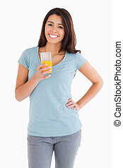 Gorgeous woman holding a glass of orange juice