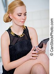 Gorgeous Woman in Black Using Tablet