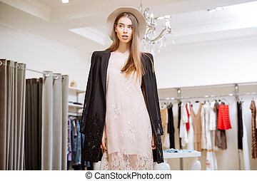 Gorgeous woman in dress, jacket and hat at clothig store