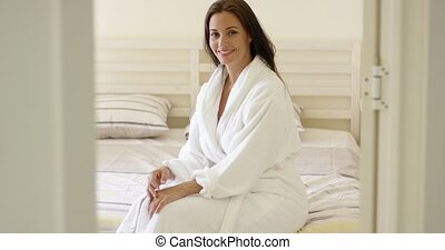 Gorgeous woman in robe sitting on bed