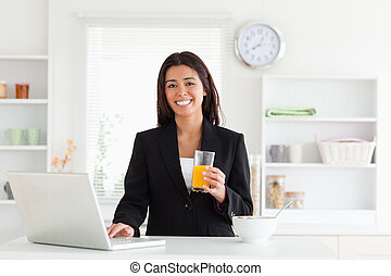Gorgeous woman in suit relaxing with her laptop while holding a glass of orange juice in the kitchen