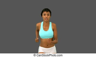 Gorgeous woman jogging on grey background