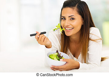 gorgeous woman lying on bed eating vegetable salad