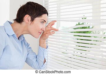 Gorgeous woman peeking out a window