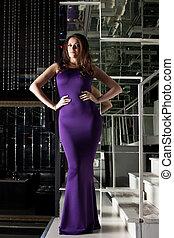 Gorgeous woman posing in long purple dress