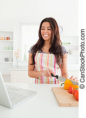 Gorgeous woman relaxing with her laptop while cooking vegetables in the kitchen