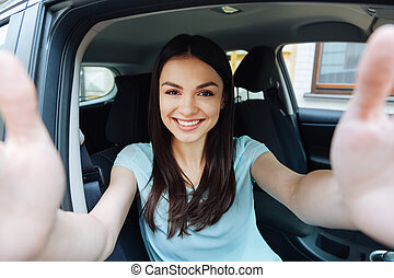 Gorgeous woman taking a picture of herself in car