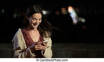 Gorgeous woman texting message on phone at night