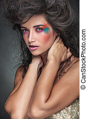 Gorgeous woman with colorful make up looking at the camera