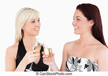 Gorgeous women in beautiful dresses toasting with champagne