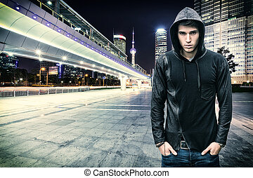 Gorgeous Young Man in Trendy Hooded Shirt Standing at the City Street While Looking at the Camera.
