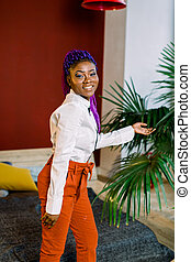 Gorgeous young african american girl , posing indoors, with blue hair. Dressed in white blouse and orange pants.