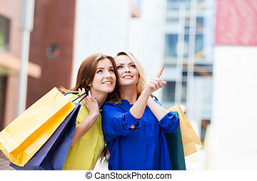 Gorgeous young blond with beautiful brunette pointing at showcase of clothing store.