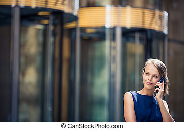 Gorgeous young businesswoman calling on her phone in front of her company's building
