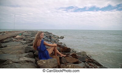 Gorgeous young girl with a beautiful figure posing and walks along the seashore