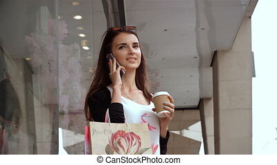 gorgeous young girl with packages worth near the shop drinkes coffee and talking on the phone