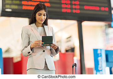 young indian businesswoman looking at air ticket