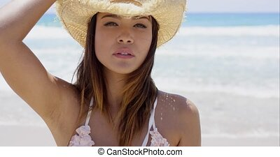 Gorgeous young sunbather wears straw hat and white bikini...