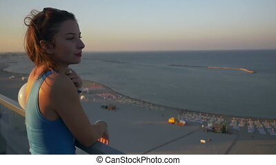 Gorgeous young teenager woman contemplating the landscape on a terrace with a sea view