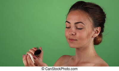 Gorgeous young woman applying makeup on green background