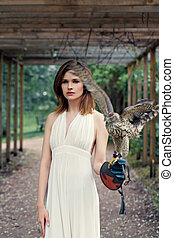 Gorgeous young woman brunette with bob haircut holding hawk bird outdoors portrait