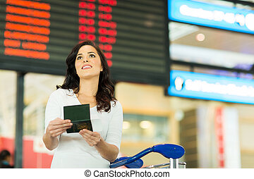 young woman checking flight information at airport