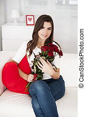 Gorgeous young woman holding bouquet of red roses