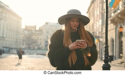 Gorgeous young woman in a bright sunlight uses her phone while standing in the city center