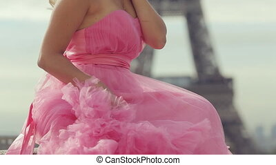 Gorgeous young woman in a magnificent pink dress posing near the Eiffel Tower