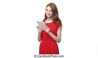 Gorgeous young woman in a orange dress uses her phone while texts back to friend. Isolated over white background.