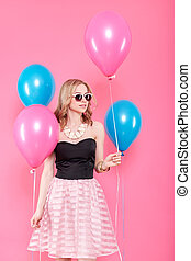 Gorgeous young woman in party outfit holding bunch of colourful balloons, isolated over pastel pink background. Birthday Party concept.