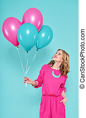 Gorgeous young woman in party summer dress holding bunch of colourful balloons, isolated over pastel blue colored background. Birthday Party concept.