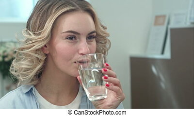 Gorgeous young woman is keeping healthy by drinking a glass of water indoors and smiling