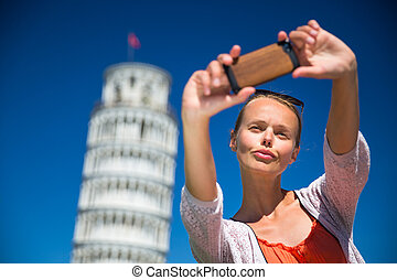 Gorgeous young woman taking a selfie with her smart phone in front of the Leaning Tower of Pisa, Tuscany, Italy