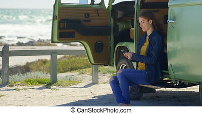Gorgeous young woman texting on mobile phone in van 4k -...