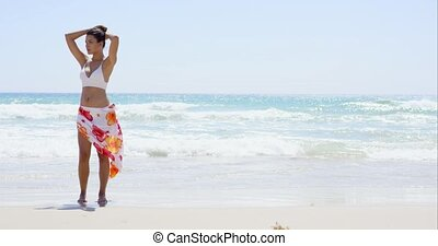 Gorgeous young woman walking along a beach